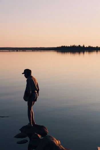 Woman standing at lakeshore against sky during sunset