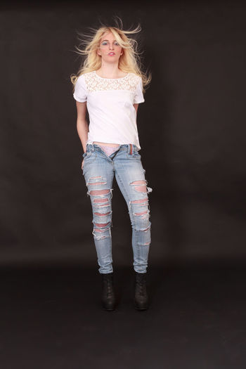 Blond girl with open jeans with holes, standing in boots before black background. The hands in the rear trouser pockets Jeans Beautiful Woman Blond Hair Careless Clothes Casual Clothing Day Front View Full Length Happiness Indoors  Jacket Leisure Activity Lifestyles Looking At Camera One Person People Portrait Real People Smiling Standing Studio Shot Sweetly Women Young Adult Young Women