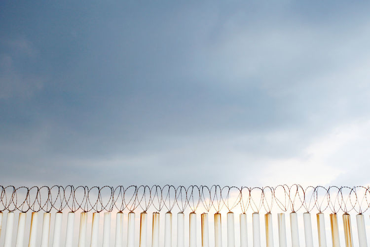Low angle view of fence against cloudy sky
