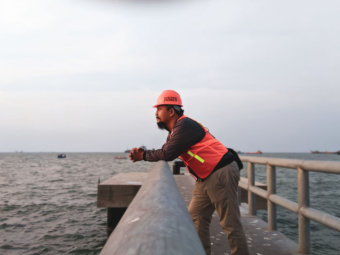 Side view of man standing by railing against sea
