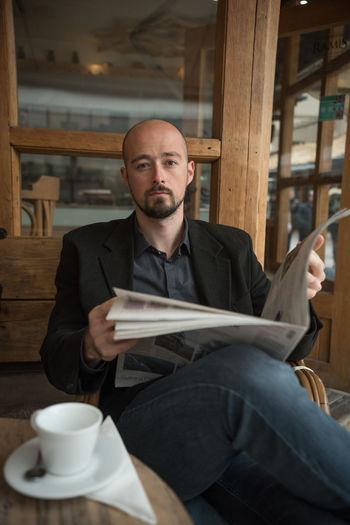 Portrait Of Businessman Reading Newspaper At Cafe