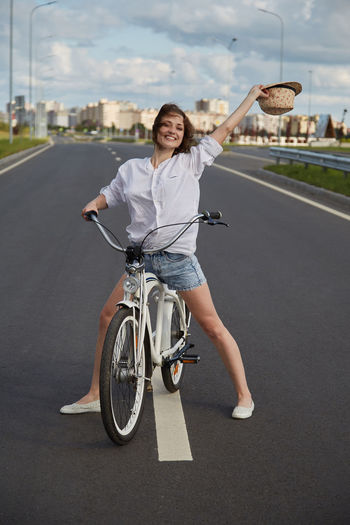 Happy young woman cyclist in white blouse and hat posing with bicycle on road smiling