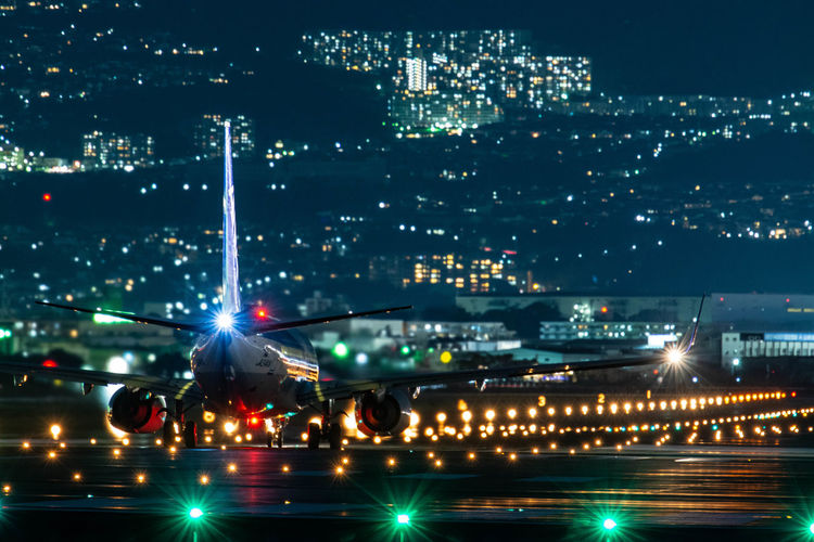 Rear view of airplane on runway at night
