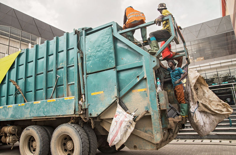 Garbage Truck Garbage Man Working Occupation Industry Transportation Day Mode Of Transportation Construction Industry Outdoors Land Vehicle Real People Sky Nature Metal One Person Architecture Stack Plastic Bag