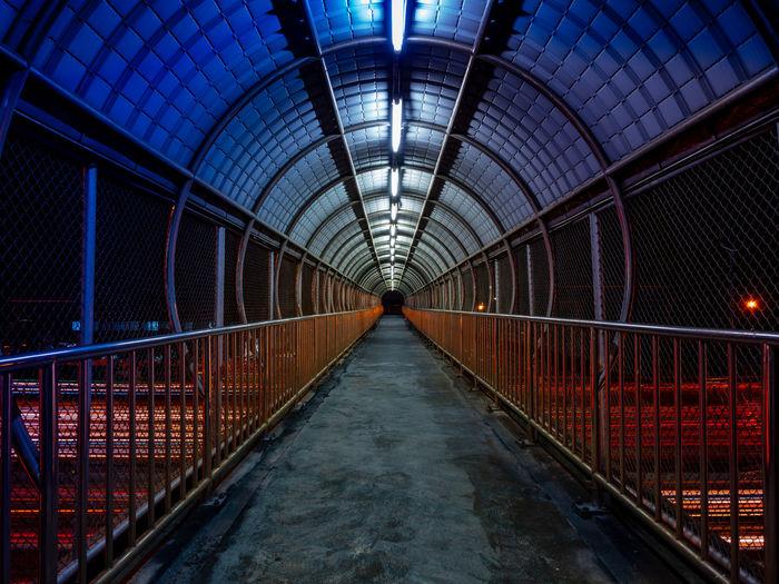 Footbridge in illuminated tunnel