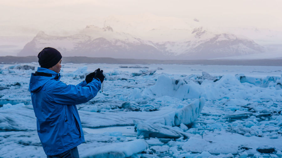 Rear view of man standing in frozen sea during winter