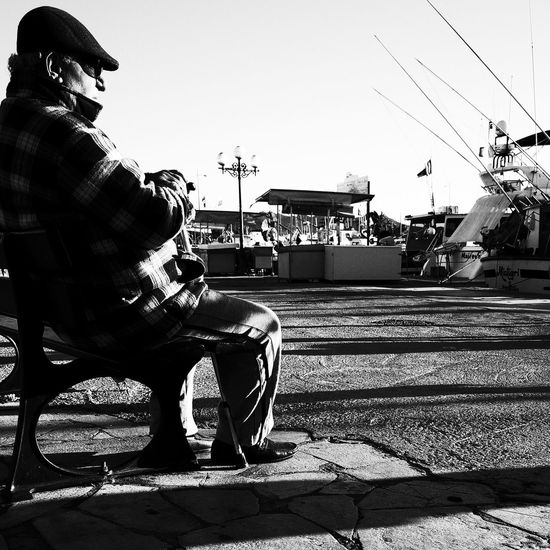 Noir Et Blanc Blackadnwhite Building Exterior Cap Day High Contrast Lifestyles Men One Person Outdoors People Real People Sitting Street Photography Streetphotography Sunlight