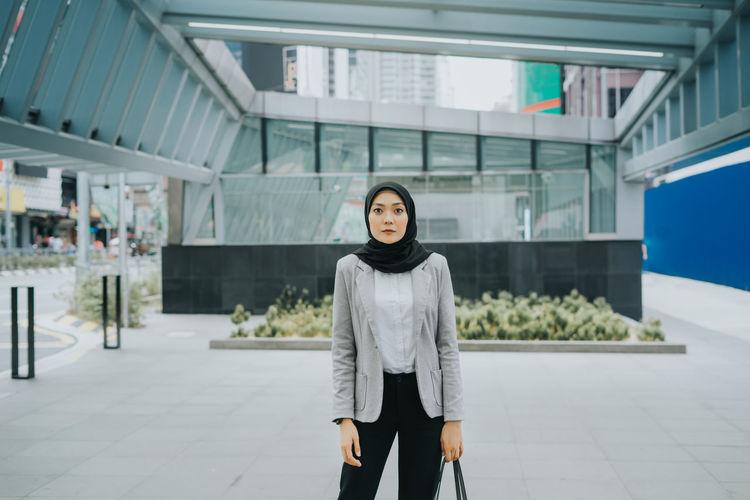 Portrait of businesswoman standing under bridge in city