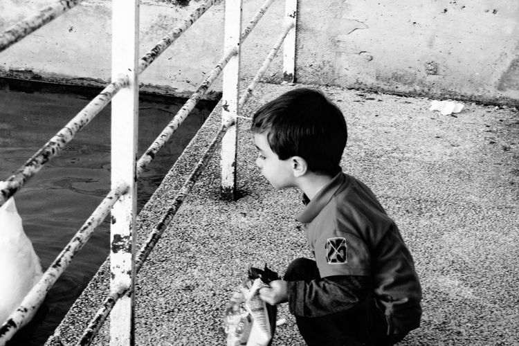 Boy holding packet crouching on promenade while looking through railing