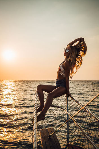 Water Sea Young Adult Leisure Activity One Person Sunset Sky Young Women Lifestyles Real People Beauty In Nature Nature Women Clothing Beauty Full Length Beautiful Woman Hairstyle Sun Horizon Over Water Outdoors