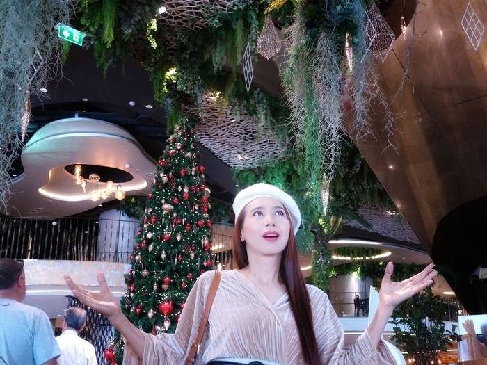 Smiling woman standing against christmas tree