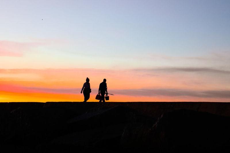 Silhouette people on sidewalk against sky during sunset