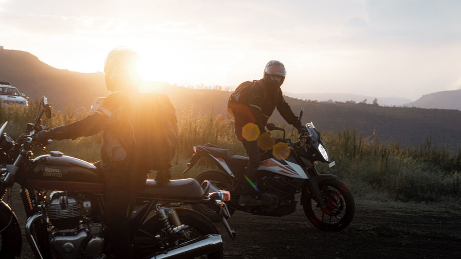 People riding motorcycle against sky during sunset