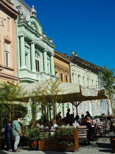 European Cities Novi Sad Serbia Eastern Europe Balkans Europe Outdoors Sunlight And Shadow Cityscape City Life Public Places Building Exterior Architecture Built Structure Day Building Street Photography City Outdoor Cafe Leisure Activity Real People Plant Adult Restaurant Tree Facades