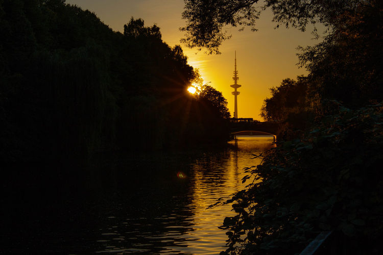 Scenic View Of River Amidst Trees During Sunset