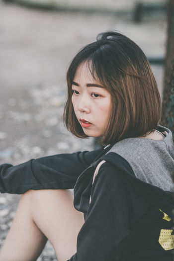 Real People Child One Person Girls Childhood Leisure Activity Women Lifestyles Hairstyle Females Casual Clothing Three Quarter Length Looking Day Focus On Foreground Portrait Sitting Innocence Hair Bangs Outdoors Teenager Contemplation