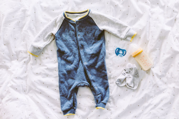 Children clothing on on the bed Baby Blue Child Childhood Close-up Clothing Cold Temperature Day Directly Above Fashion Hanging High Angle View Indoors  Nature No People Snow Still Life Textile White Color Winter Womenswear
