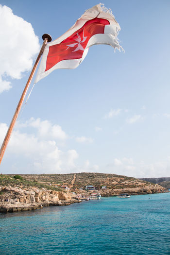 Flag Sky Water Environment Cloud - Sky Nature Day Sea Wind Architecture Outdoors Freedom Blue Low Angle View Built Structure Independence National Icon Flag Of Malta Comino Island Malta Comino Travel Photography Travel Destinations Blue Sky And Clouds Blue Lagoon Malta
