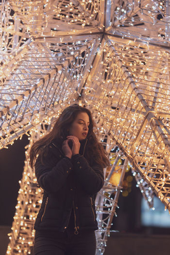 Woman Wearing Warm Clothing Against Illuminated Decoration At Night