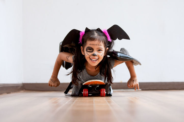 Portrait of cute playful girl with spooky make-up lying on skateboard at home during halloween