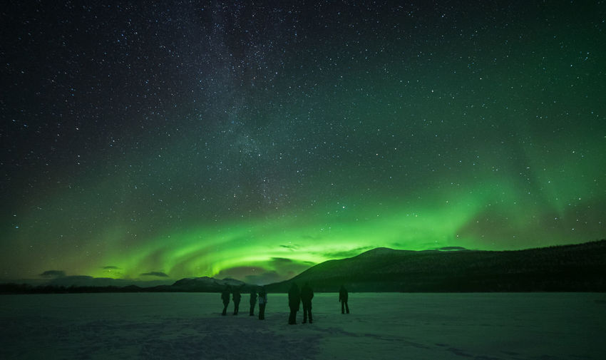 Silhouette people on land with aurora borealis in sky at night