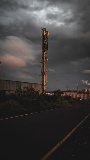 Communications tower on land against sky at sunset