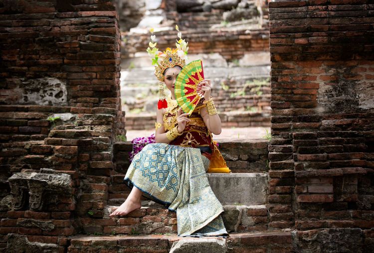 Young woman in traditional clothing holding hand fan while sitting at temple