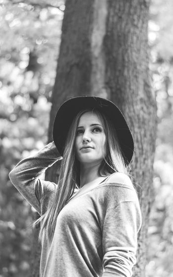 Young woman with long hair wearing hat looking away