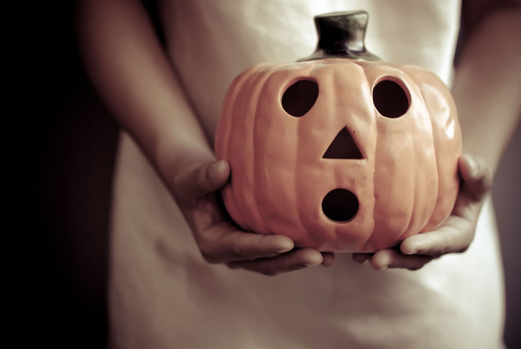 Close-up of woman hand holding jack o lantern during halloween