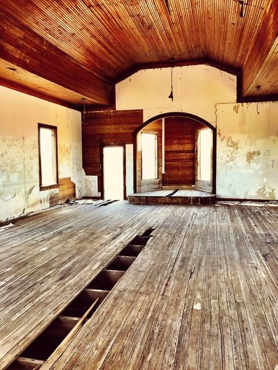 """""""To Reach Heaven You Must Cross The Void"""" The interior sanctuary of the Taiban Presbyterian Church, built in 1908, lies alone and ghost like in the town of Taiban, New Mexico. Churches New Mexico Photography New Mexico Abandoned Buildings Abandoned Places Ghosttown Ghostly Wood Floor Interior Santuary Church Architecture Built Structure Building No People Sunlight Abandoned"""