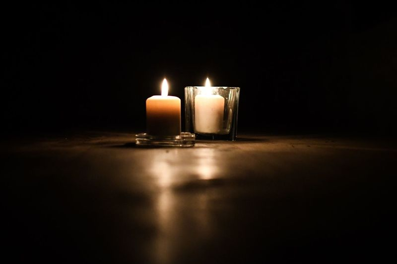 Close-up of illuminated tea light candles on table in dark room