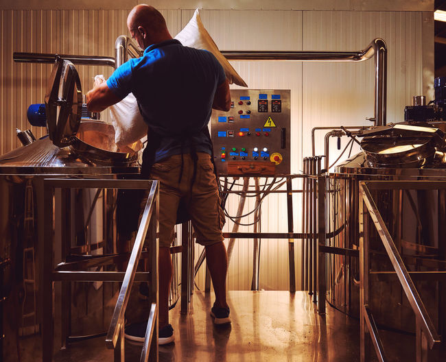 Rear View Of Man Working In Brewery
