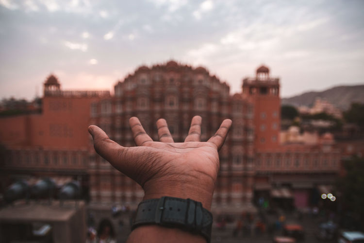 Cropped image of person hand against building in city against sky