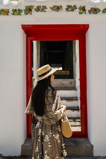 Rear view of woman wearing hat against doorway