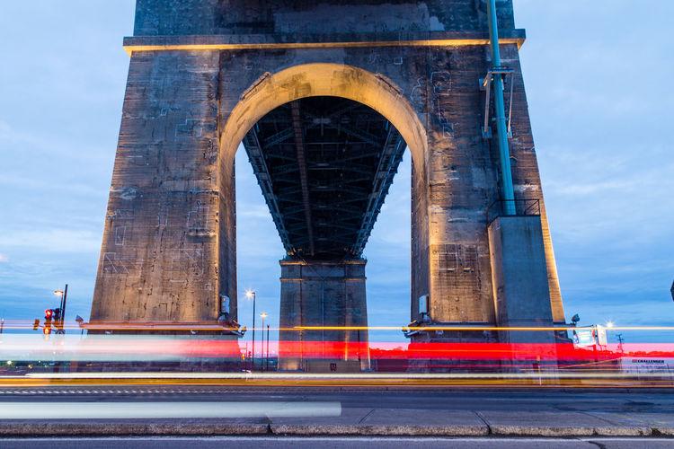 Blurred motion of light trails against bridge