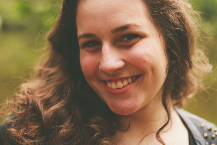 Close-up portrait of smiling teenage girl at park