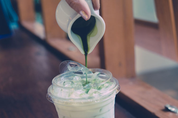 Pouring the green tea into the milk, make a cup of Matcha latte. (vintage tone) Body Part Close-up Container Finger Focus On Foreground Food And Drink Glass Glass - Material Green Color Hand Holding Human Body Part Human Finger Human Hand Indoors  Lifestyles One Person Real People Table Unrecognizable Person