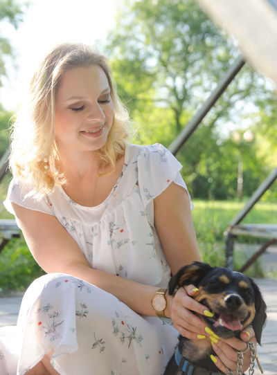 Smiling young woman with dog in park