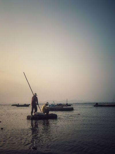 Men in boat on sea against clear sky