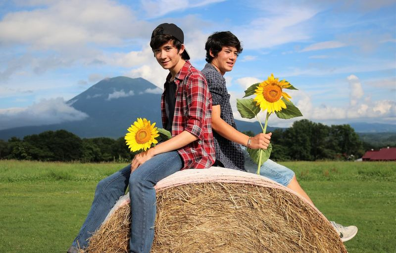 Boys Holding Sunflowers While Sitting On Hay Bale Against Sky