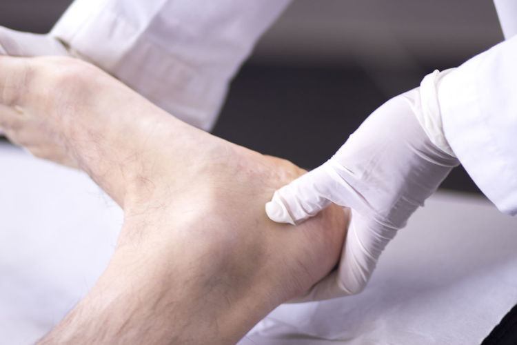 Cropped hands of doctor examining leg