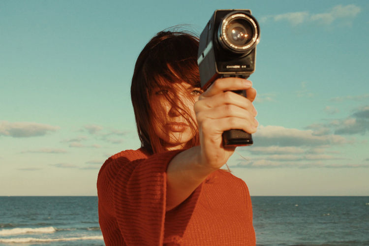 Woman photographing with camera against sea and sky