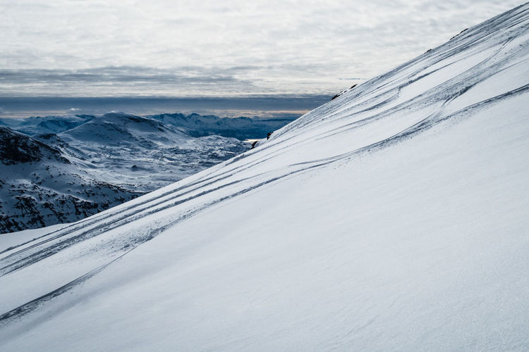 Snow covered mountain with ski tracks against sky