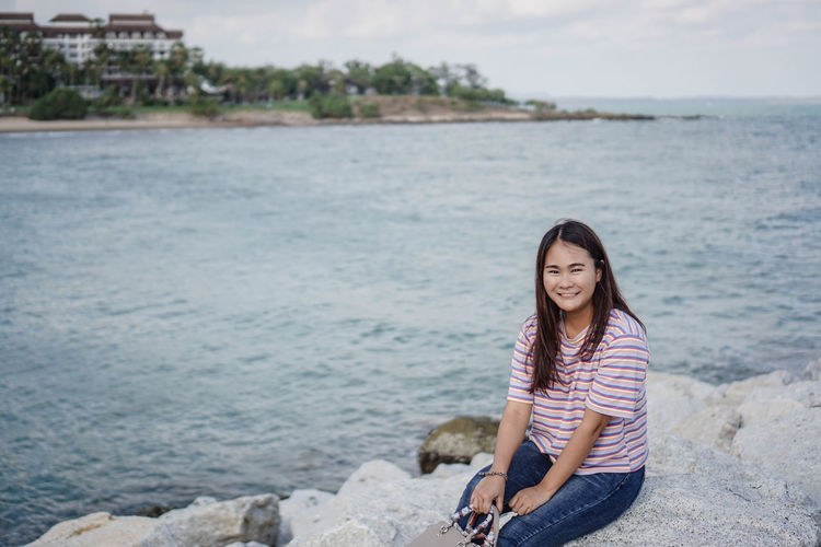 Portrait of smiling woman sitting on rock by sea against sky
