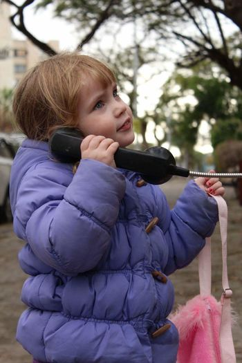 Close-up of girl in warm clothing talking on telephone while standing at street