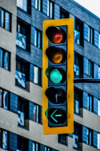 Low angle view of road signal against illuminated building