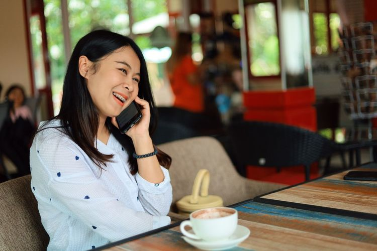Table Food And Drink Drink One Person Young Women Young Adult Happiness Sitting Communication Casual Clothing Focus On Foreground Restaurant Holding Cup Smiling Cafe Using Phone Women Wireless Technology Glass Outdoors