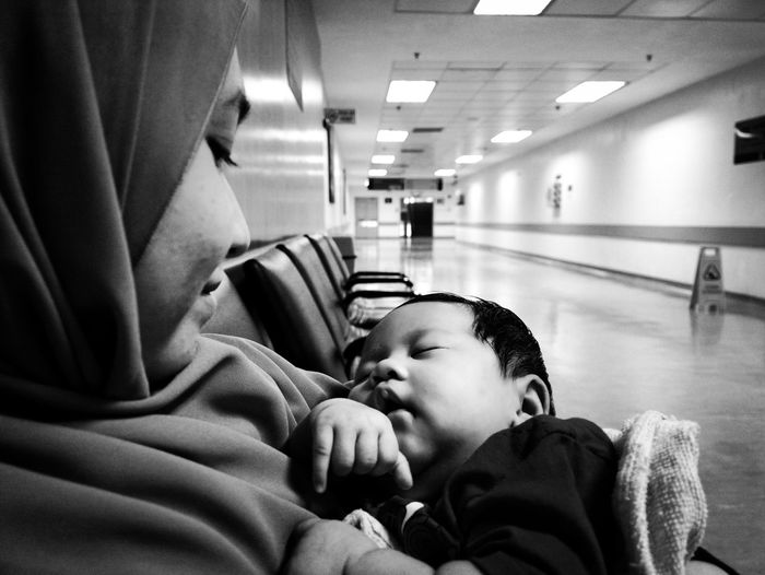 Side view of woman with baby girl sitting on bench in hospital