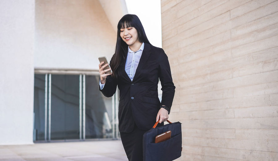 Smiling businesswoman using mobile phone while standing against wall