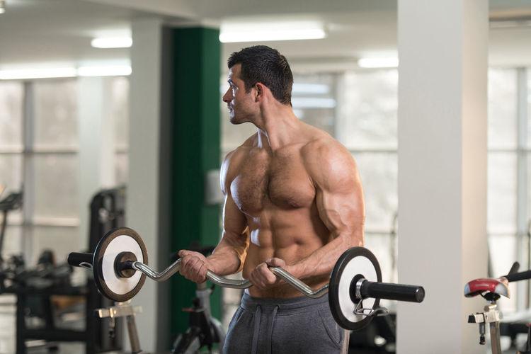 Shirtless young man exercising in gym
